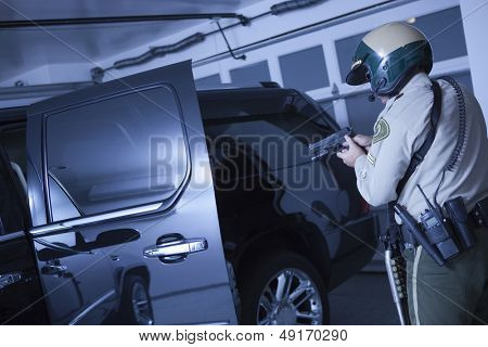 Rear view of middle aged traffic cop aiming handgun at car in garage