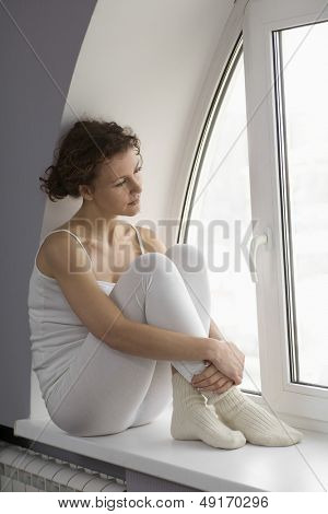 Full length of thoughtful woman sitting on window sill