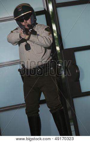 Middle aged policeman aiming handgun against door