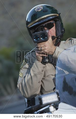 Middle aged policeman monitoring speed through radar while sitting on bike