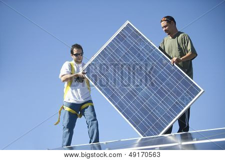 Young interracial engineers holding solar panel againat blue sky