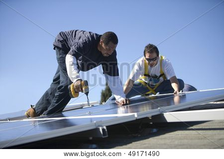 Two engineers working on solar panels against blue sky