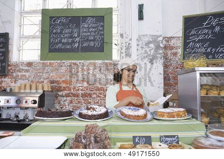 Middle aged female owner working at counter in cake shop
