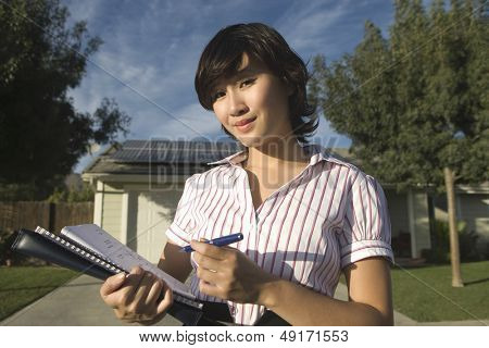 Portrait of young female solar panel worker working on blueprint outdoors