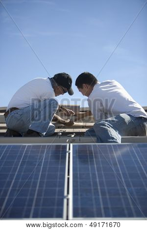 Two engineers working on solar panelling at rooftop against blue sky