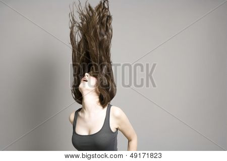 Young woman tossing long brown wavy hair against gray background