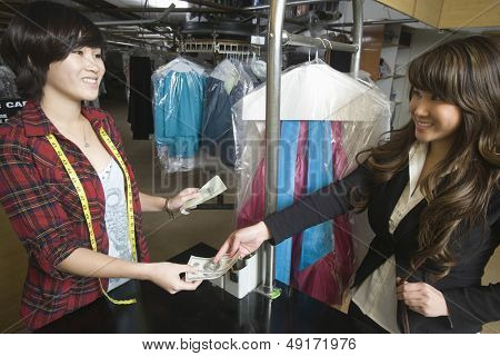 Happy young female customer paying money to laundry owner
