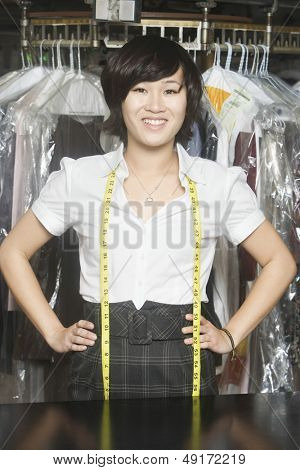 Portrait of happy young woman with hands on hips standing against clothes rail in laundry