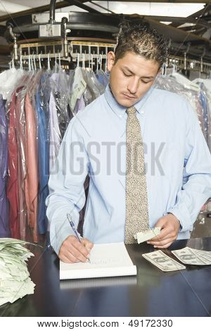 Young laundry owner with receipts and banknotes analyzing accounts at counter