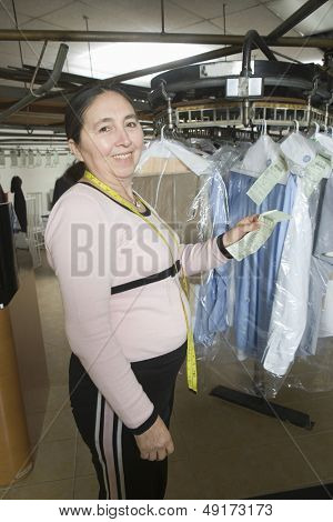 Portrait of middle aged female owner with receipt standing by clothes rail in laundry