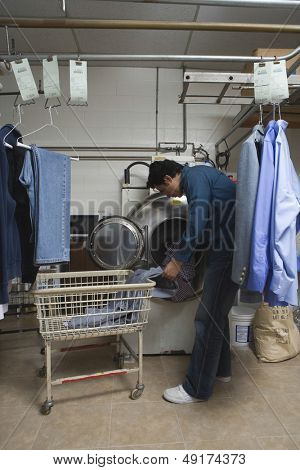 Full length of young man loading clothes in washing machine at laundry