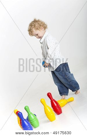 Toddler is playing with colorful tenpins
