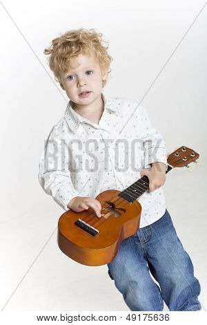 Young boy is playing with ukulele