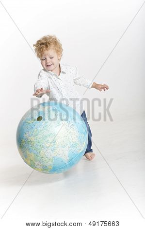 Toddler is bouncing a big globe
