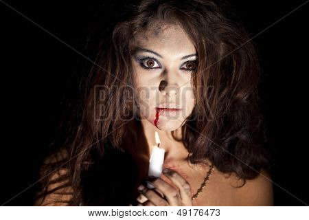 Frightened girl with a candle in hands