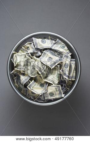 Dollar bills in wastebasket view from above