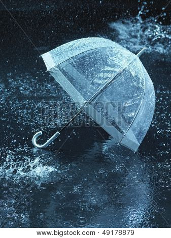 Unused umbrella lying on ground being rained upon