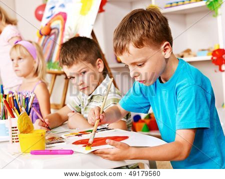 Children painting at easel in school. Education.