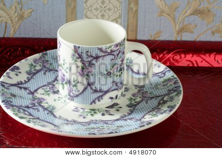 Taza de té de estilo antiguo de Inglaterra y el plato sobre bandeja roja