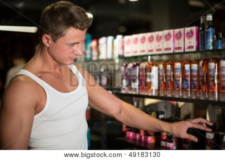 MOSCOW - JAN 24: Muscular man looking at the items in the department of oils and creams in Museum-Shop Point G on Novy Arbat on January 24, 2013 in Moscow, Russia.