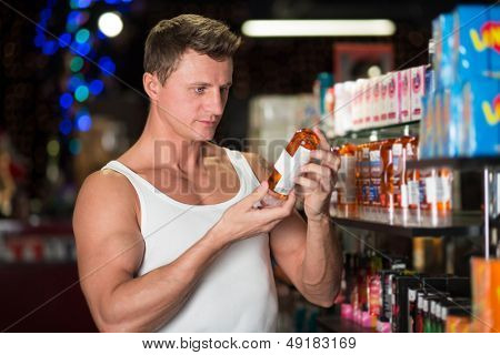 MOSCOW - JAN 24: Muscular man chooses items in the department of oils and creams in Museum-Shop Point G on Novy Arbat on January 24, 2013 in Moscow, Russia.