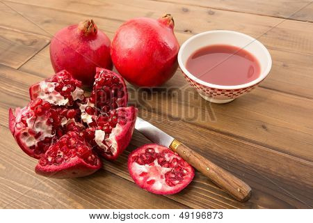 Juicy pomegranates fresh and cut on a wooden table