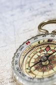 stock photo of cartographer  - Old compass on a cartographic map of mountains - JPG