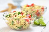 stock photo of tabouleh  - Fresh homemade Tabbouleh an Arabian vegetarian salad made of couscous tomato cucumber onion garlic parsley and lemon juice served in a glass bowl (Selective Focus Focus one third into the tabbouleh)