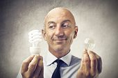 bald businessman holding two light bulbs