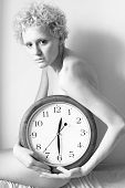 Young scrawny woman with big clock in hands (b/w photo)