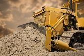 stock photo of heavy equipment operator  - Bulldozer at work on the orange sky background - JPG
