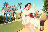 Elvis look-alike impersonator man in front of Welcome to Fabulous Las Vegas sign on the strip. Peopl
