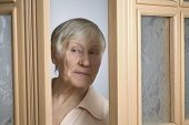 Beautiful elderly woman peeking through doorway at home