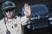 image of traffic signal  - Confident middle aged traffic cop signaling stop gesture with car in background - JPG