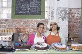 stock photo of cake stand  - Portrait of happy mother and daughter in aprons standing at cake shop counter - JPG