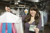 picture of receipt  - Portrait of happy young woman holding dry cleaned clothes and receipt in laundry - JPG