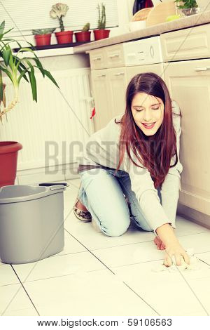Young happy woman cleaning flor on her knees