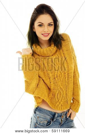 Trendy beautiful young woman in a gold pull-over and jeans giving a thumbs up of approval as she smiles at the camera, on white