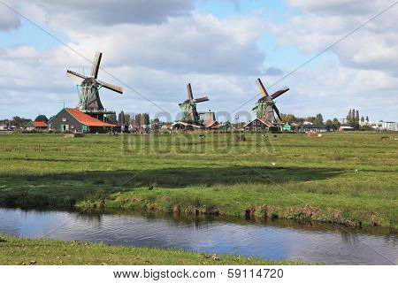 The village - an ethnographic museum in Holland. Three windmills on a green meadow, among deep channels