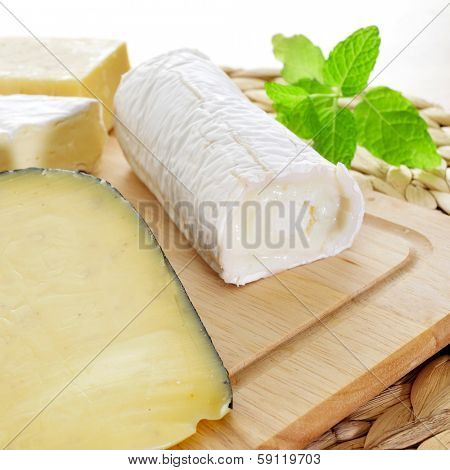 closeup of a wooden chopping board with an assortment of cheese, such as goat cheese, spiced cheese or Brie cheese