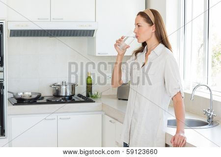 Side view of a young woman drinking water in the kitchen at home