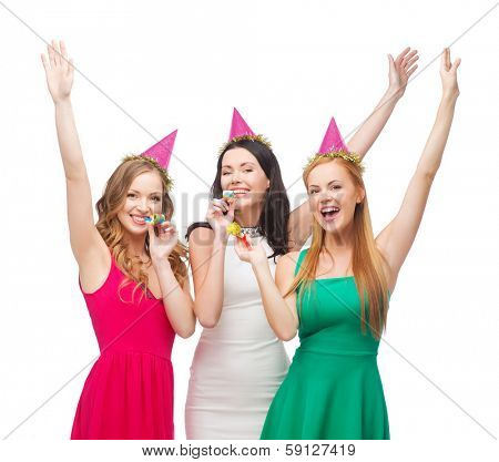 celebration, friends, bachelorette party, birthday concept - three smiling women wearing pink hats and blowing favor horns and waving hands