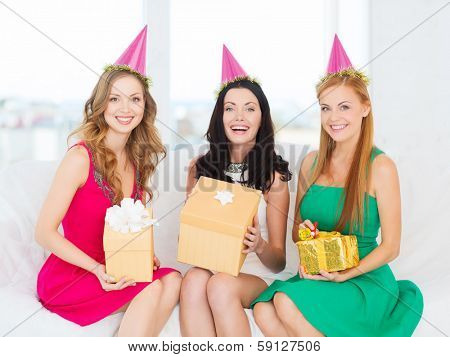 celebration, friends, bachelorette party, birthday concept - three smiling women wearing pink hats with gift boxes