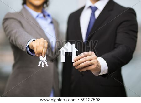 business, eco, real estate and office concept - businessman and businesswoman holding white paper house and keys in office