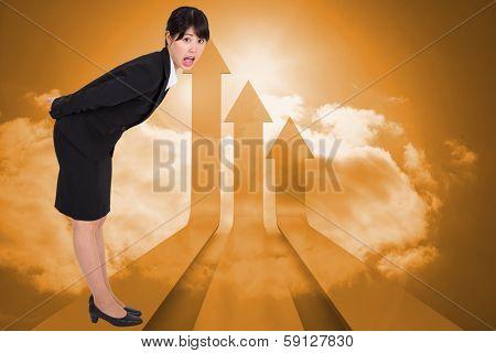 Surpised businesswoman bending against arrows in the sky in orange
