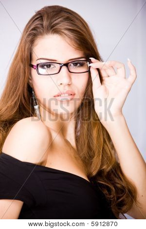 young woman with long brown hair touching her glasses