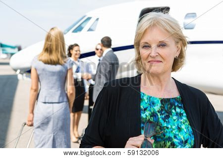 Portrait of confident businesswoman with airhostess greeting business people near private jet