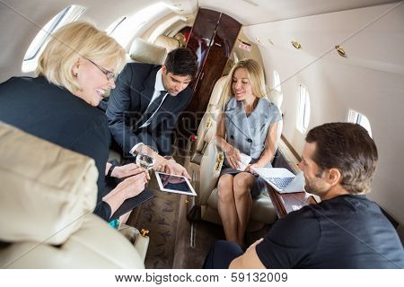 Businessman showing presentation on digital tablet with colleagues in corporate jet