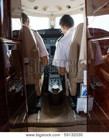 Rear view of pilot and copilot operating private jet