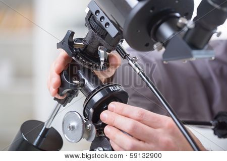 Man's hand on astroniomical telescope adjusting its settings.